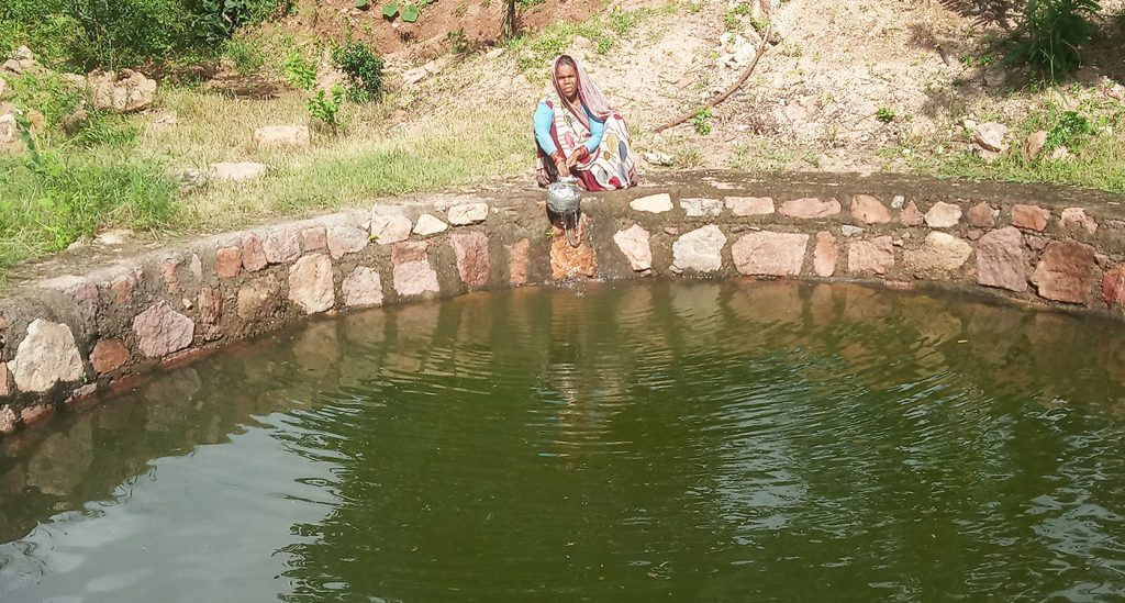 A woman collects water from a well that was recharged due to water harvesting in Lalitpur district of Bundelkhand.